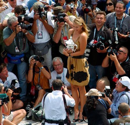2006年の全米オープンで優勝し、トロフィーを手にカメラマンに囲まれるマリア・シャラポワ=ニューヨーク(AP=共同)