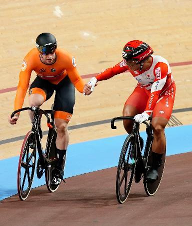 男子スプリント準々決勝でラブレイセン(左)に敗れ、握手する新田祐大=ベルリン(共同)