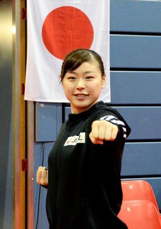 空手の組手女子61キロ超級で東京五輪代表を確定させ、日の丸の前でポーズをとる植草歩=2月29日、ザルツブルク(共同)