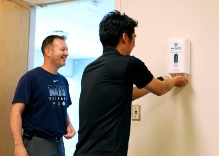 筒香が所属する米大リーグ、レイズのキャンプ地で、記者席に設置された消毒剤を使用する日本人記者(右)=2日、ポートシャーロット(共同)
