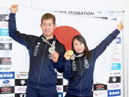 日の丸を掲げ自転車トラック種目世界選手権で獲得したメダルを手にする脇本雄太(左)と梶原悠未=3日、成田空港