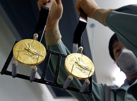 メッキ液から引き揚げられた、2020年東京五輪の金メダル=4日、大阪市の造幣局