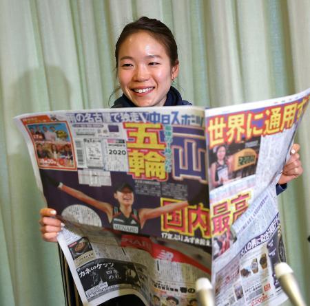 名古屋ウィメンズマラソンから一夜明けの記者会見で、自身の優勝と五輪代表決定を報じる新聞を手に笑顔の一山麻緒=9日、名古屋市