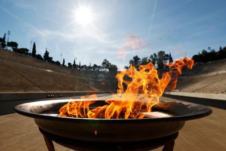 ギリシャ国内のリレーが打ち切りとなり、アテネのパナシナイコ競技場で聖火台にともされた東京五輪の聖火=14日(共同)