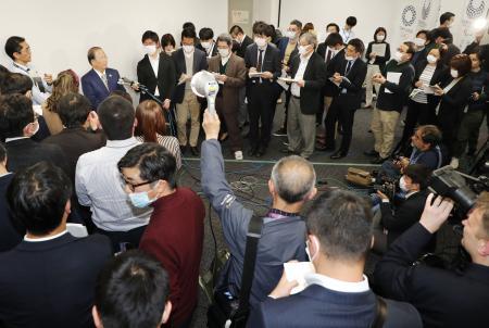 大勢の報道陣に囲まれ、取材に応じる東京五輪・パラリンピック組織委員会の武藤敏郎事務総長(奥左から2人目)=17日午後、東京都内