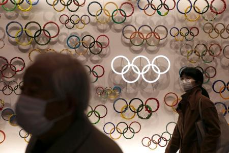 五輪博物館「日本オリンピックミュージアム」に展示された五輪マークと、マスクをした入場客=2月、東京(AP=共同)
