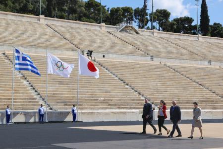 無観客で行われた東京五輪の聖火引き継ぎ式。右から3人目は元五輪競泳代表の井本直歩子さん=19日、アテネのパナシナイコ競技場(代表撮影・共同)