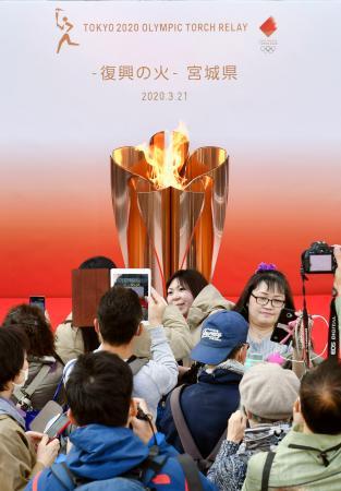 「復興の火」プロジェクトの一環として、JR仙台駅で公開された東京五輪の聖火の前で記念撮影する人たち=21日午後