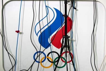 2019年12月、ドーピング問題での記者会見で掲示されたロシア五輪委のロゴ。報道陣のマイクの配線が垂れ下がる=モスクワ(AP=共同)