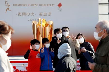 「復興の火」として展示された東京五輪の聖火の前で記念撮影する人たち=25日午後、福島県いわき市