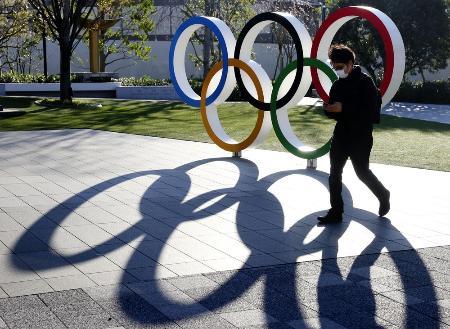 五輪マークのモニュメントの前をマスク姿で歩く人=東京都新宿区
