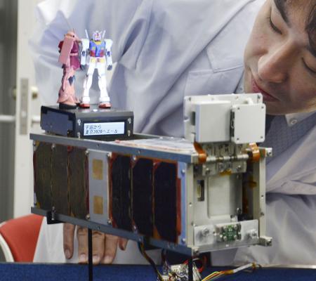 「機動戦士ガンダム」の模型を載せた超小型衛星のレプリカ=2019年12月、東京都港区