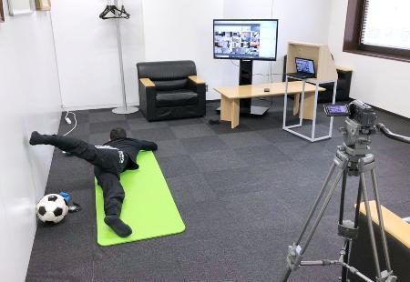 オンラインを活用した横浜Mの練習で、体幹トレーニングの手本を見せるコーチ(横浜M提供)