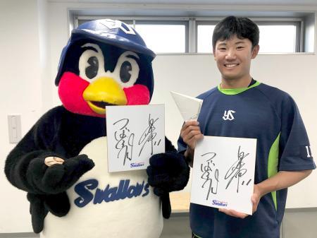 ファンにプレゼントするサイン色紙を持つヤクルトの奥川とつば九郎=3月、埼玉県戸田市の球団施設(同球団提供)