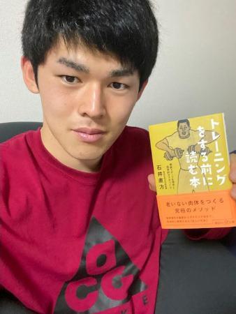 最近読んだというトレーニングに関する本を手にするロッテ・佐々木朗(球団提供)