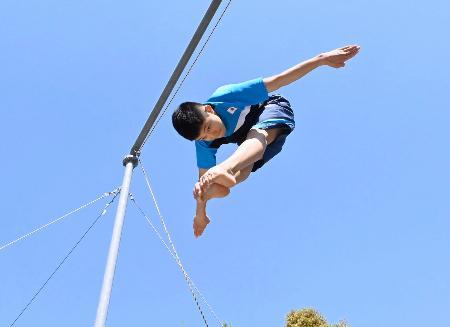 跳躍器具を使い、屋外で練習する男子高飛び込みの玉井陸斗(ジエブ提供)
