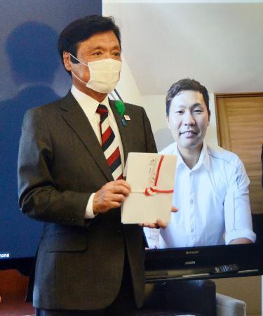 ソフトバンクの中村晃選手(右)から目録を受け取った福岡県の小川洋知事=11日午後、福岡県庁