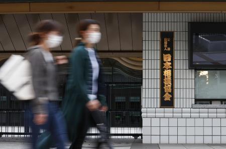 東京・両国国技館の前を通るマスク姿の人たち
