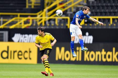 再開したサッカーのドイツ1部リーグで、競り合うドルトムントのフンメルス(左)とシャルケのラマン=16日、ドルトムント(AP=共同)