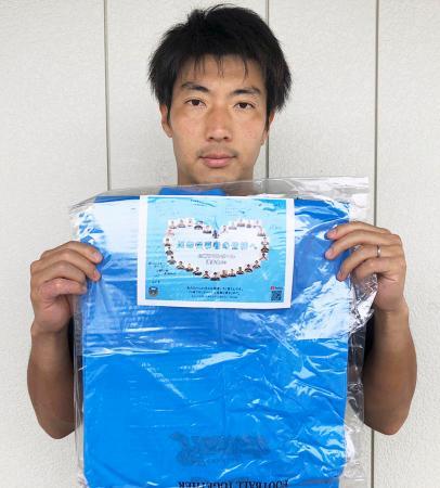 医療機関に寄付するポンチョを持つJ1川崎フロンターレの安藤駿介選手会長=川崎市(クラブ提供)