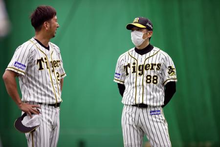マスクを着け、甲子園の室内練習場で藤川(左)と話す阪神の矢野監督(球団提供)