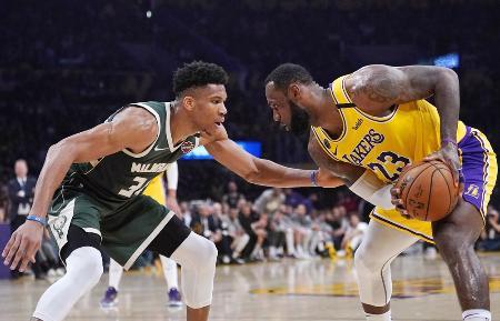 米プロバスケットボールNBAで、攻めるレーカーズのジェームズ(右)と守るバックスのG・アデトクンボ=3月、ロサンゼルス(AP=共同)