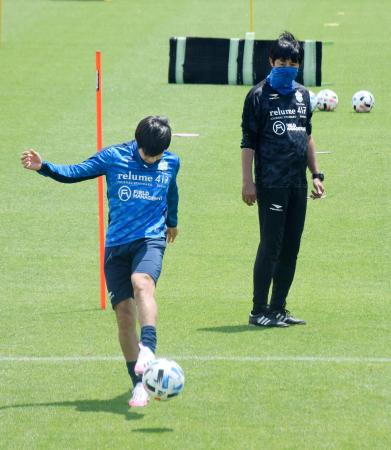 マスクを着用し、練習を見守る湘南の浮嶋監督。左はMF山田=神奈川県平塚市