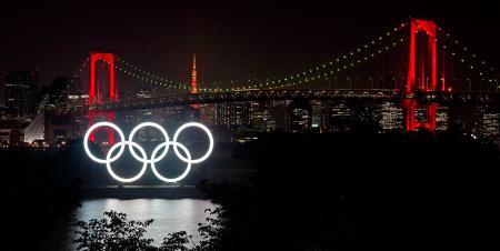 「東京アラート」が継続され、赤くライトアップされたレインボーブリッジ(奥)と五輪マークのモニュメント=4日夜、東京臨海部