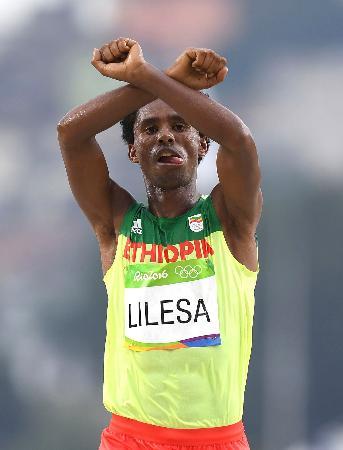 2016年リオデジャネイロ五輪の男子マラソンで、抗議のポーズをとってゴールするエチオピア選手(ゲッティ=共同)