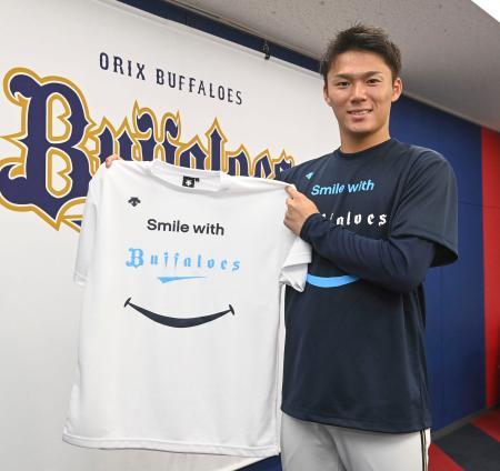 「野球で笑顔に」のTシャツを見せるオリックス・山本=13日