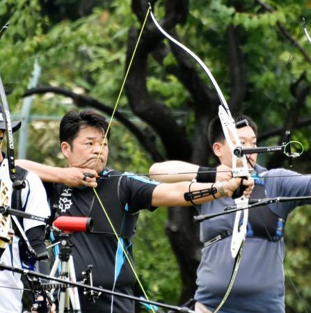 アーチェリーの記録会に参加し、弓を引くアテネ五輪銀メダリストの山本博(左)=横浜市