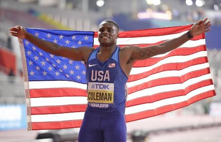 世界陸上男子100メートルで優勝し、笑顔で星条旗を掲げる米国のクリスチャン・コールマン=2019年9月、ドーハ(共同)