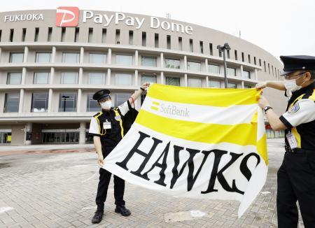 ペイペイドーム前に掲揚する、ソフトバンクの球団旗を広げる警備員=19日午前、福岡市