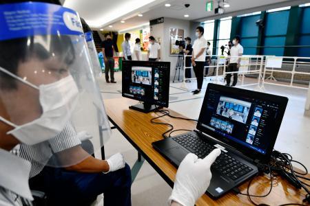 新型コロナウイルス感染対策で、検温作業の甲子園球場関係者=23日午前、兵庫県西宮市