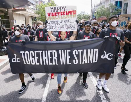 ワシントンでNBAウィザーズの選手とデモ行進するWNBAミスティックスのクラウド(中央)=19日、ワシントン(UPI=共同)