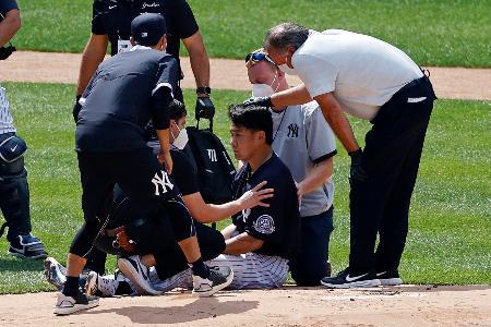 練習中に打球を頭部に受け、医療チームから手当を受けるヤンキースの田中(中央)=4日、ニューヨーク(AP=共同)