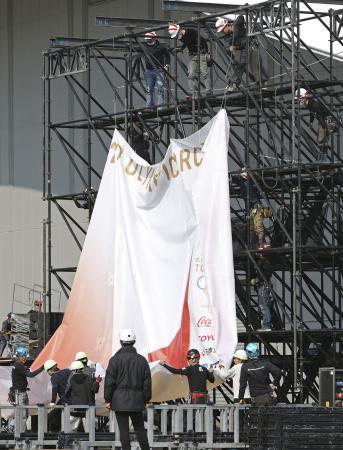 東京五輪聖火リレーのスタート地点、福島県のサッカー施設「Jヴィレッジ」で取り外される垂れ幕=3月26日