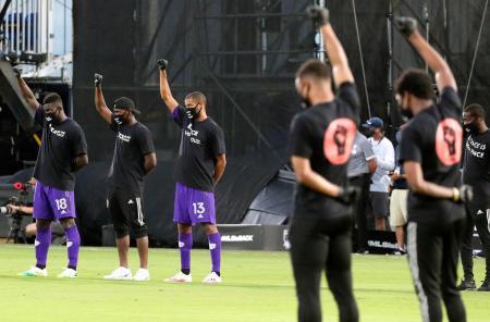 サッカー米プロリーグMLSの試合前、ピッチ上で反人種差別デモを行う黒人選手たち=8日、フロリダ州オーランド近郊(AP=共同)