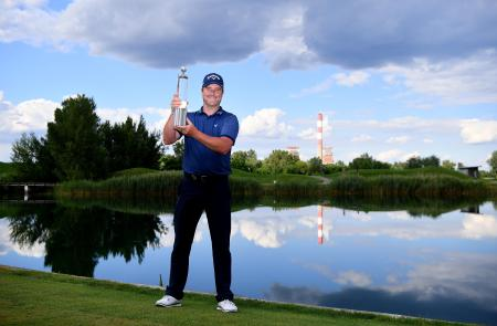 欧州ゴルフのオーストリア・オープンを制し、トロフィーを掲げるマーク・ウォーレン=12日、アッツェンブルーク(ゲッティ=共同)