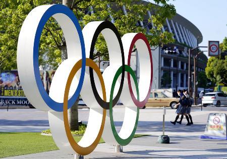 東京五輪・パラリンピックの開閉会式会場となる国立競技場(奥)と五輪マークのモニュメント=6月、東京都新宿区