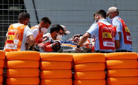 オートバイの世界選手権シリーズでレース中に転倒し、担架で運び出されるマルク・マルケス(中央)=19日、ヘレスデラフロンテラ(ロイター=共同)