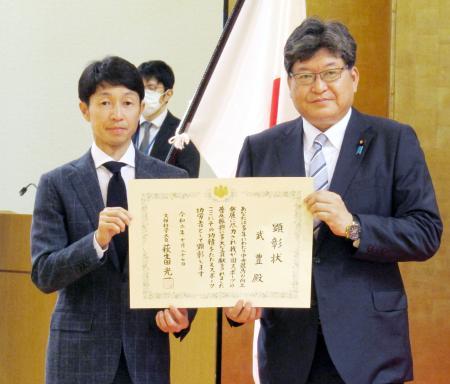 「スポーツ功労者」として顕彰された武豊騎手。右は萩生田文科相=27日午後、文科省