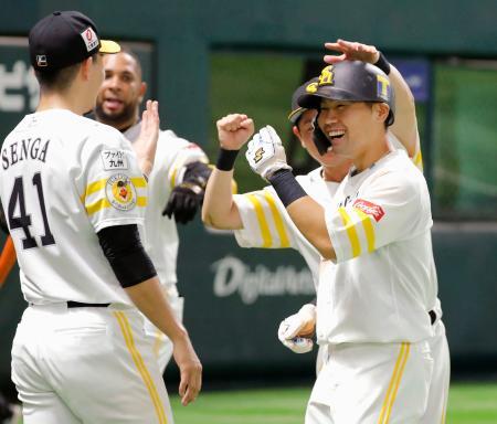 6回、走者一掃の勝ち越し二塁打を放ち、千賀(41)らナインに迎えられるソフトバンク・中村晃=ペイペイドーム