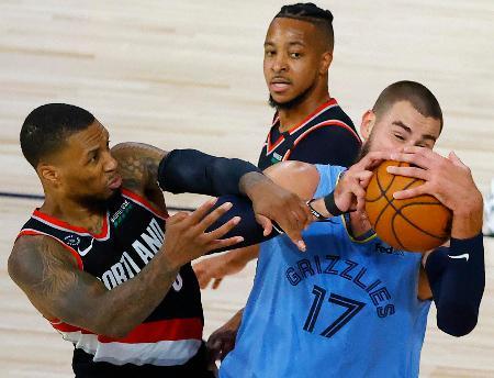 NBAのプレーオフ進出決定戦、ボールを奪い合うトレイルブレーザーズのリラード(左)とグリズリーズのバランチューナス=15日、レークブエナビスタ(AP=共同)