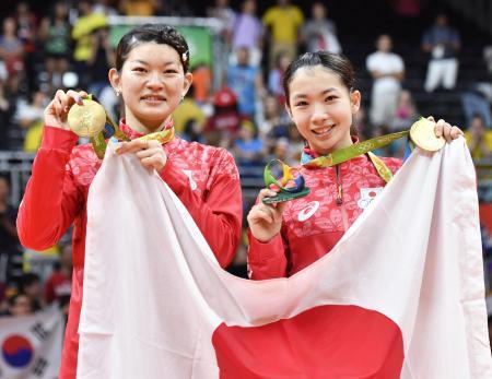 リオデジャネイロ五輪のバドミントン女子ダブルスで優勝し、笑顔で金メダルを手にする高橋礼華(左)と松友美佐紀=2016年8月(共同)