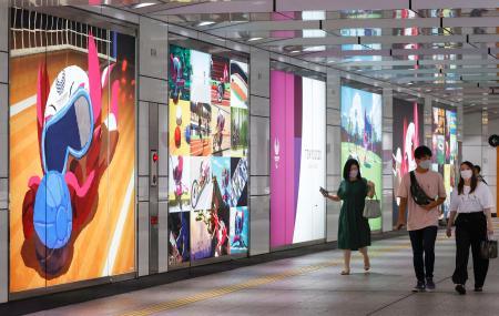 新型コロナウイルスの影響で異例の延期となった東京パラリンピックは24日で開幕まで1年。大会マスコットが競技をPRするパネルが掲げられた東京都庁近くの通路を、マスク姿の人たちが行き交っていた=23日午後、東京・西新宿