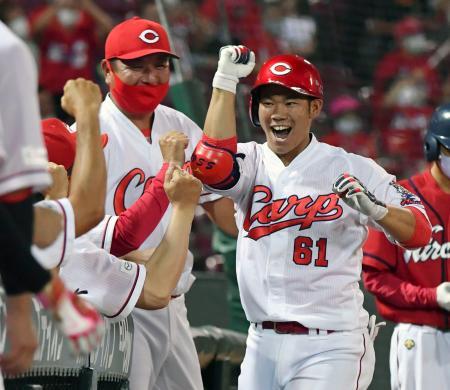8回、代打で勝ち越しソロを放ちナインに迎えられる広島・坂倉(右)=マツダ