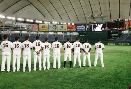 DeNA戦の試合前、故川上哲治氏の背番号「16」のユニホーム姿で大型スクリーンの映像を見る巨人ナイン=東京ドーム