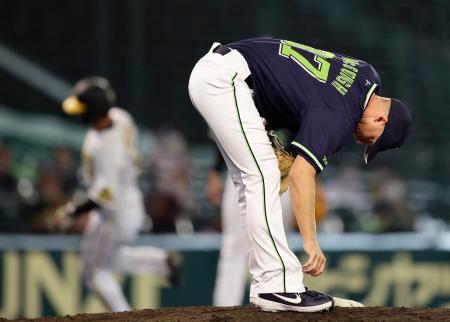 7回、阪神2死二、三塁、打者近本のとき、一塁にけん制を悪送球しうつむくヤクルトのマクガフ(右)。2点を許した=甲子園