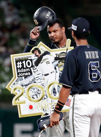 5回、日米通算2千安打となる適時二塁打を放ち、記念のボードを手にするオリックスのジョーンズ=メットライフドーム